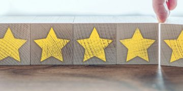 five star quality service rating on wooden blocks, customer feedback concept